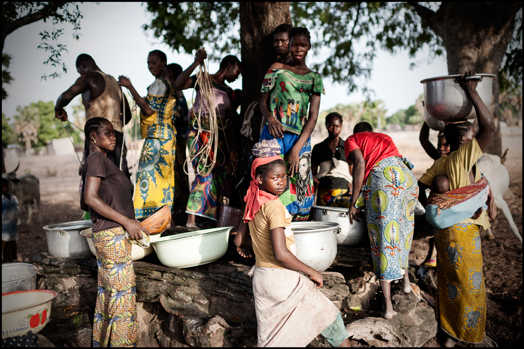 A girl, surrounded by other girls and women, looks into the camera at Mokolo Kambaya, Tandjilé, Chad  on 27 April 2015 . The 15 meter deep water well is the only water source within a radius of 20 km and so, some women have sometimes to walk for hours to get fresh water.