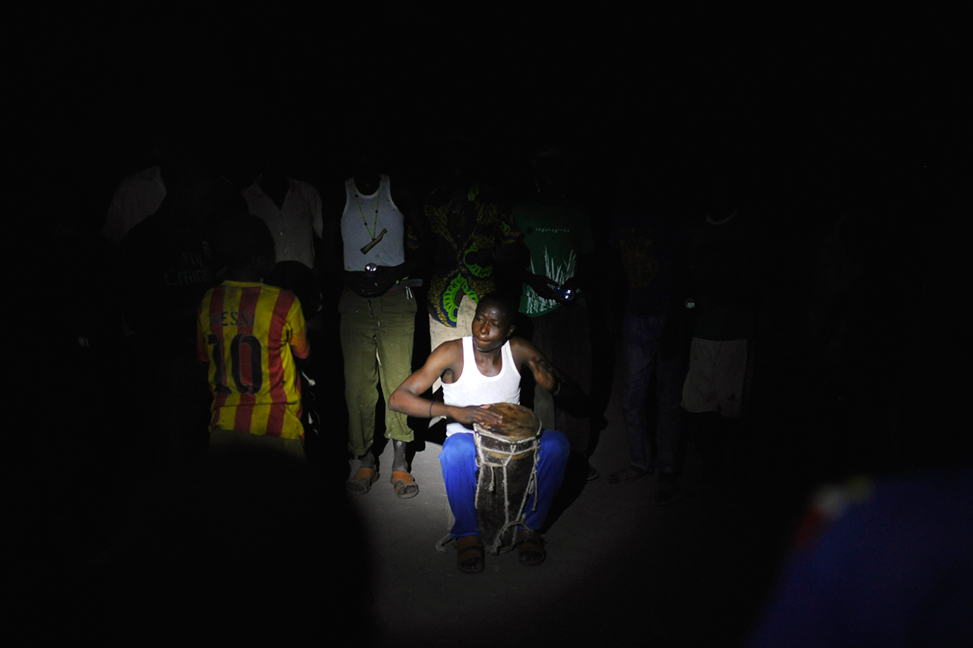 """A boy plays a """"tam-tam"""" atMokolo Kambaya, Tandjilé,Chad in the middle of the night on 25April2015. Young catholics celebrate and dance near the catholic church without having electricity and without light. People got more and more scared of starting a fire or of dancingand singing becauseof Boko-Haram."""