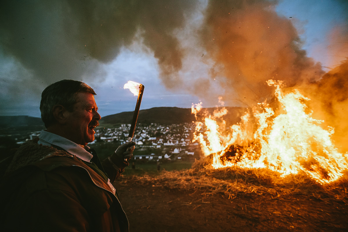 A man observes the great Easter fire in Lügde, Germany, 27 Mars 2016. After sparking the Easter fire members of Lüdge's Dechen association push burning wheels down a hill. The Easter wheels herald the end of the winter now and then symbolizing the sun and being part of a centuries-old rite.