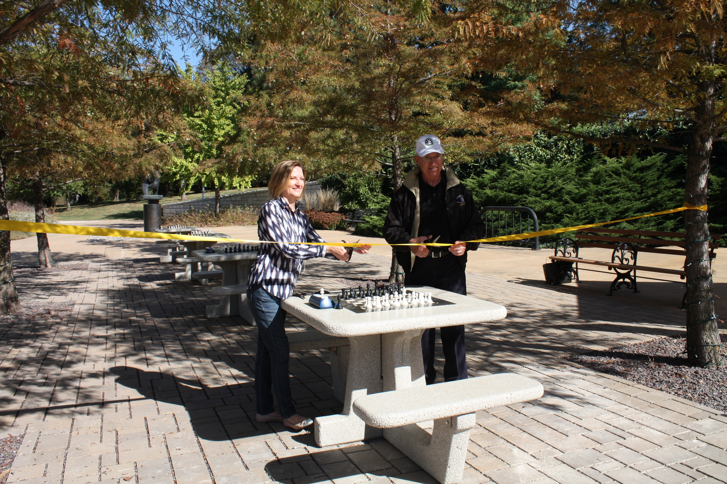 Forest Park Forever President and Executive Director Lesley S. Hoffarth, P.E. cuts the ribbon on Forest Park's new chess plaza with Rex Sinquefield, founder of the Chess Club and Scholastic Center of Saint Louis