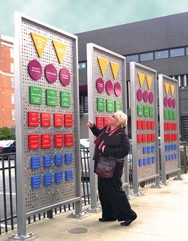 Heather Neff of Heurista taking in the outdoor donor wall with its movable marbles.