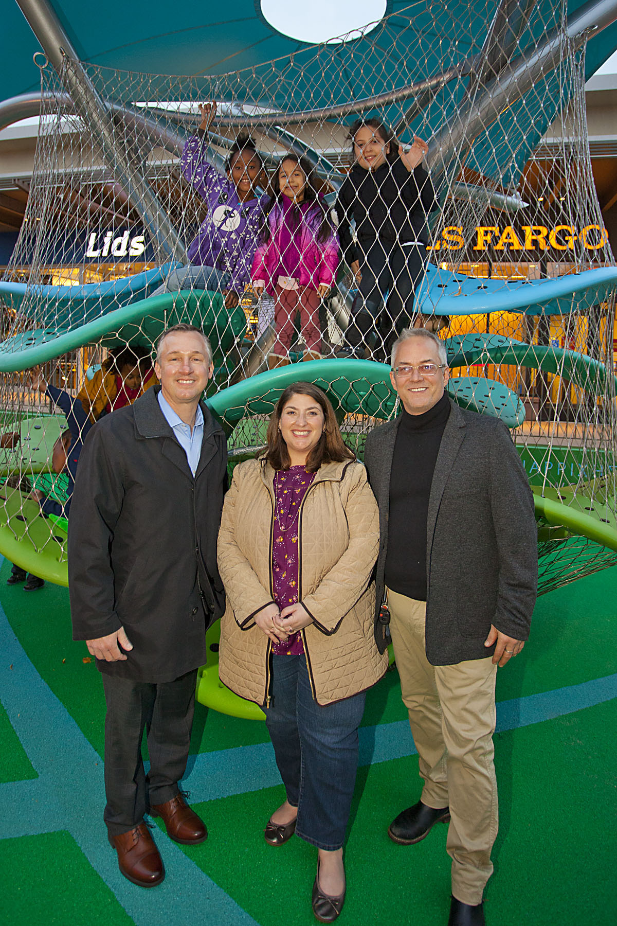 Picture here: children at play during the grand opening, Carl Calabro and Liz Pollack from Cross County Shopping Center, and Heurista's Ed Manner