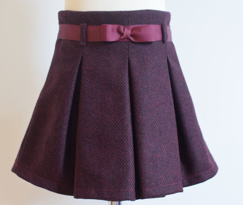 Burgundy wool skirt   Description: pretty pleats front and back, matching grosgrain ribbon belt, concealed zip at side, adjustable elastic waist  Sizes: available in 6y. All other sizes sold out  £34