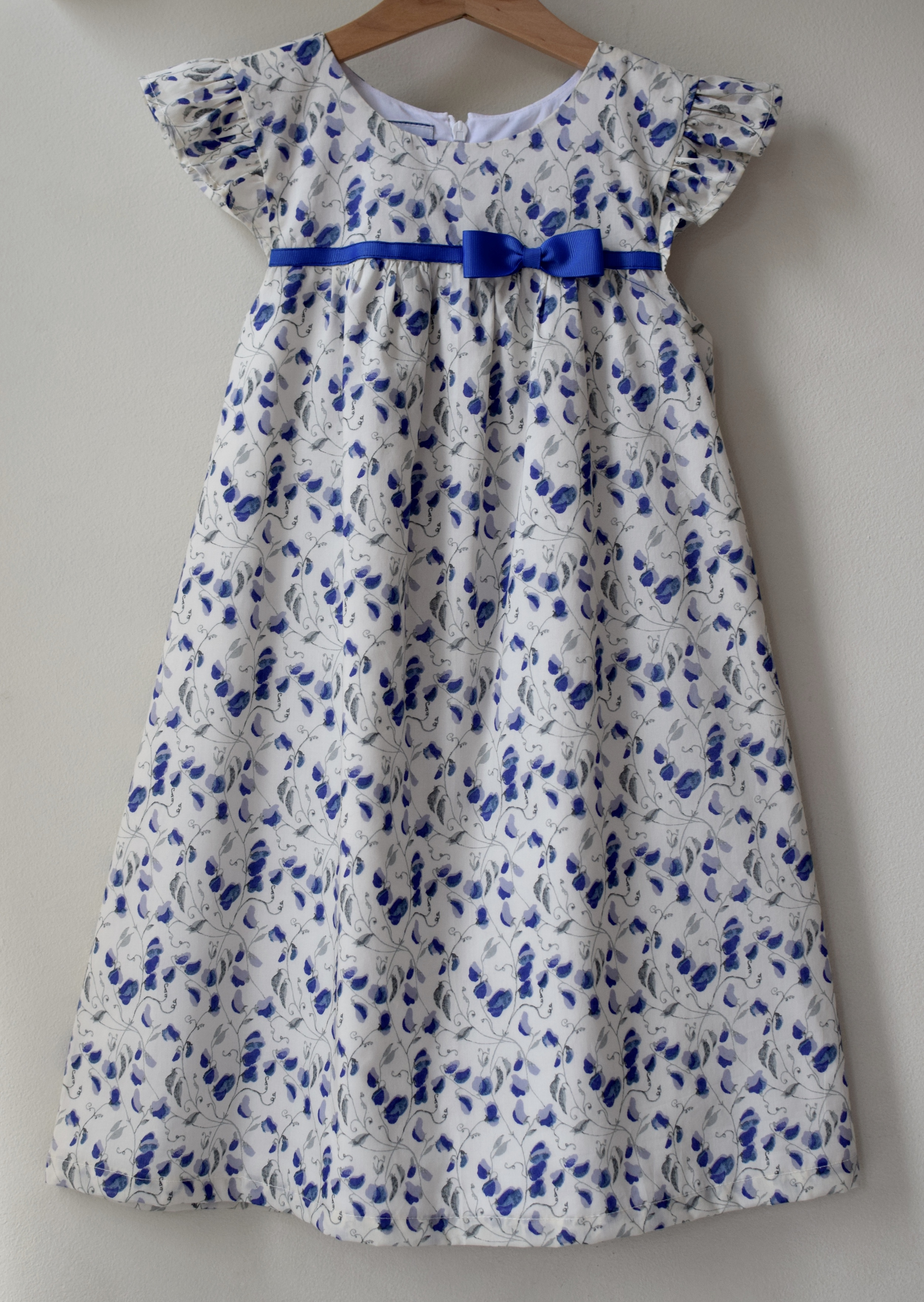 Blue sweetpea ruffle dress £43   Liberty print dress with ruffle sleeves available exclusively in size 6y. Fully lined with a concealed zip at the back, fixed contrasting blue grosgrain ribbon and round neck detail.