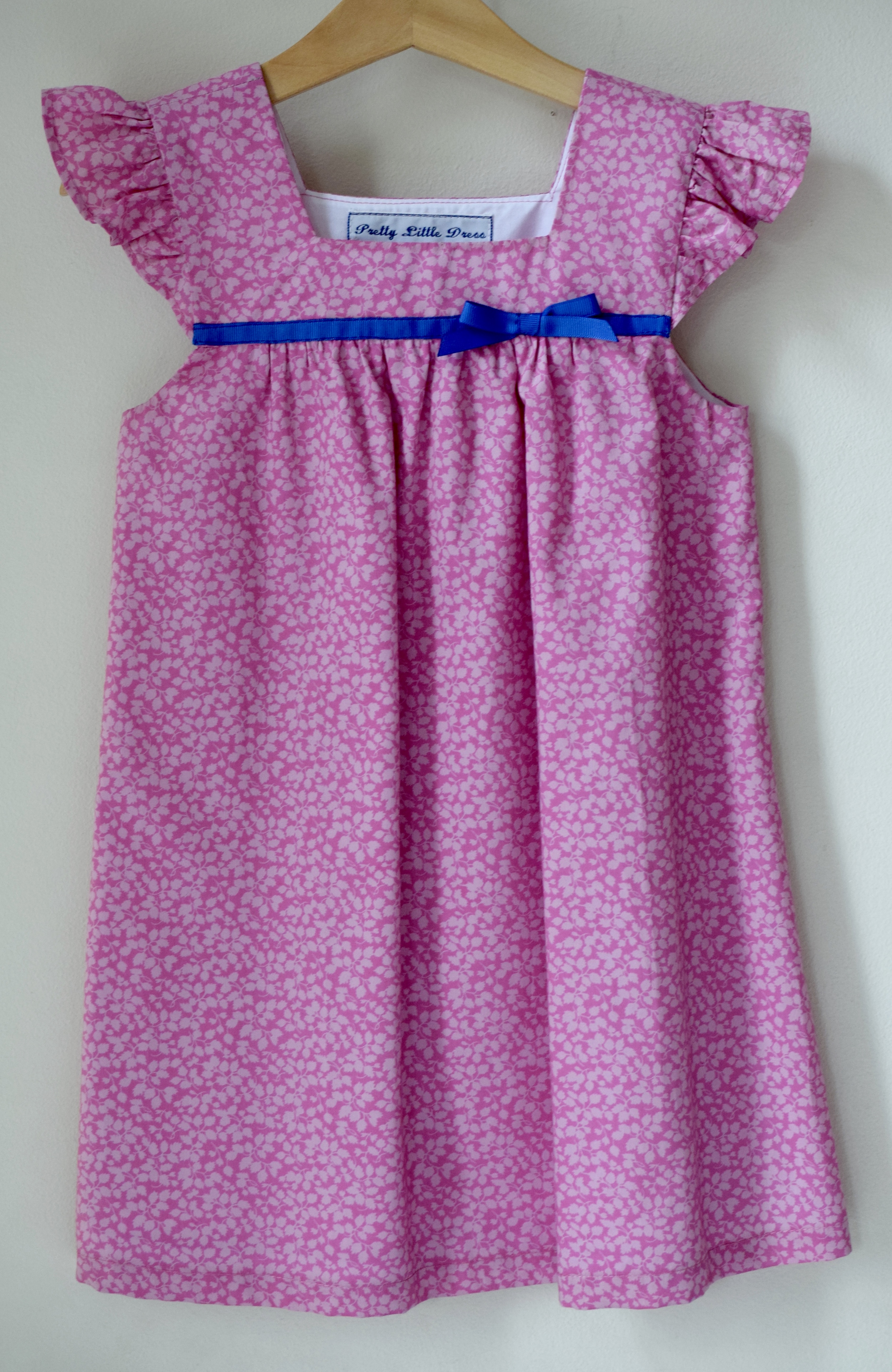 Pink Glenjade ruffle Dress £43   Liberty print dress with ruffle sleeves and square neck detail. Fully lined with a fixed contrasting blue grosgrain ribbon detail.Available exclusively in size 4y.
