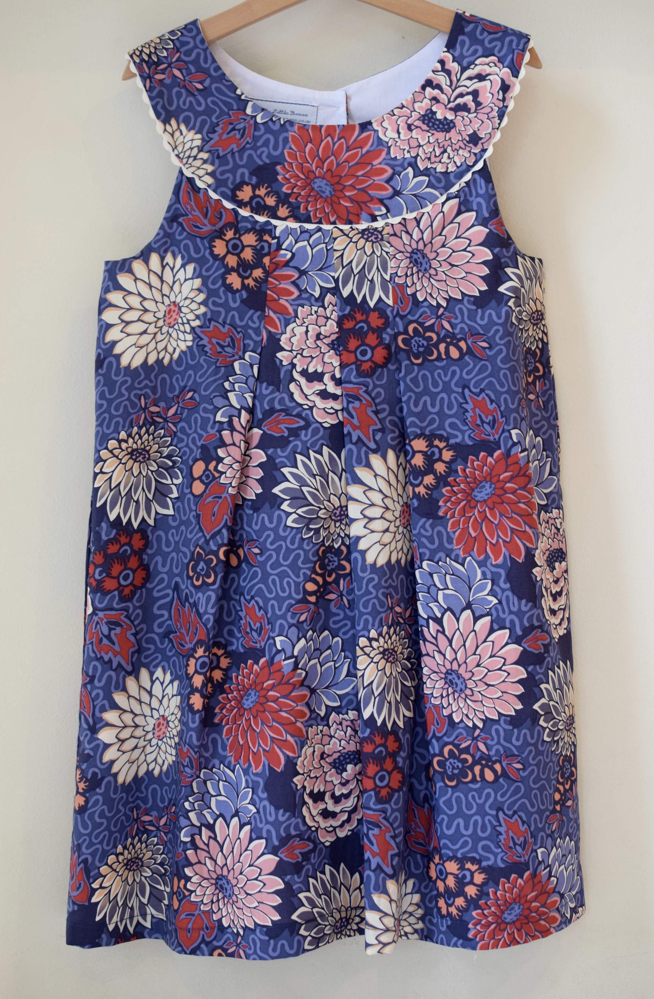 Meandering Chrysanthemums pink and blue Dress £43   Liberty print sleeveless dress with a round neck, fully lined and contrasting rick rack ribbon detail. Available exclusively in size 6y.