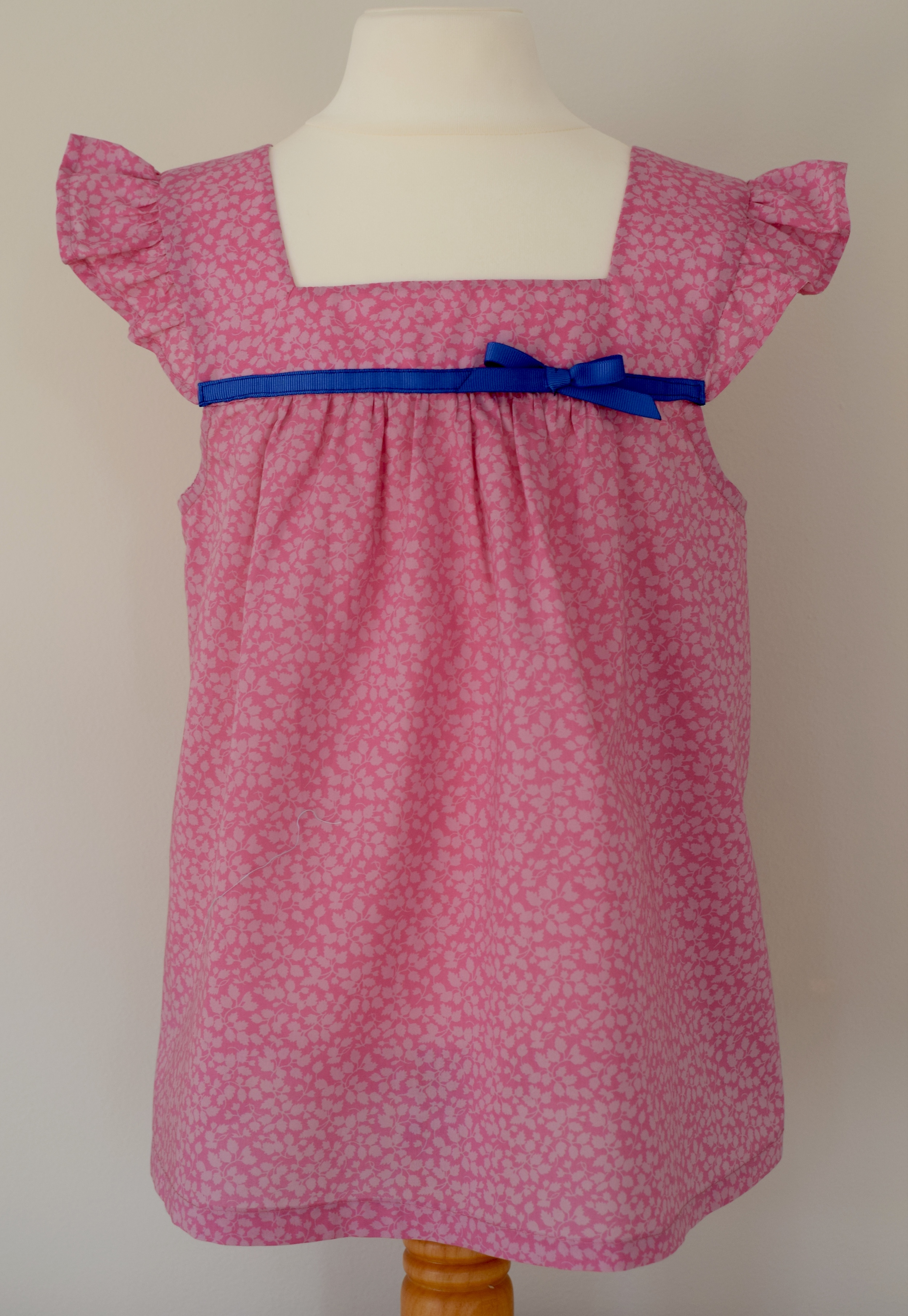 Liberty Glenjade pink   Liberty print, ruffle sleeves, square neck top with a fixed contrasting blue grosgrain ribbon.  Available in size large  £35