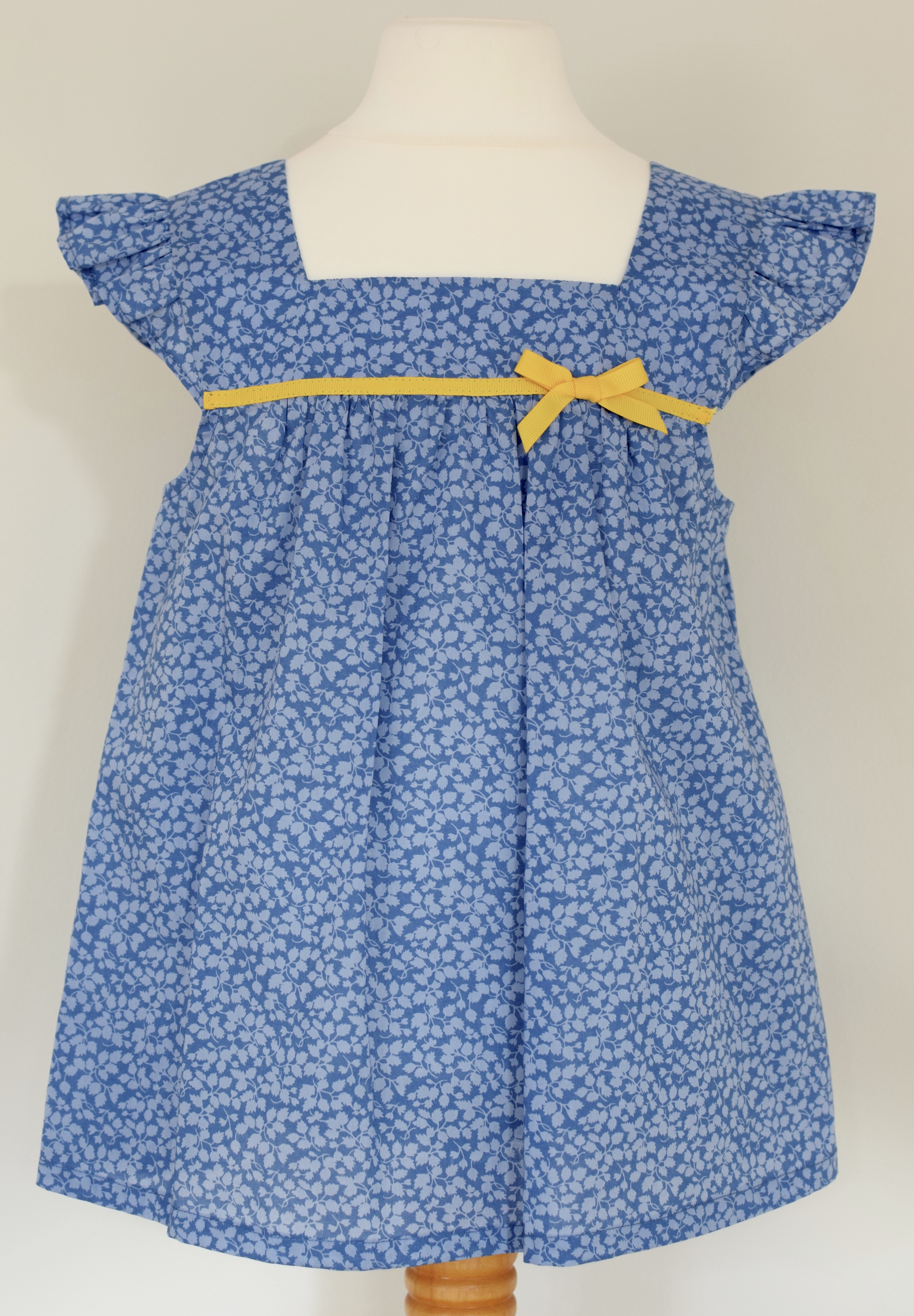 Liberty Glenjade blue   Liberty print,ruffle sleeves, square neck top with a fixed yellow grosgrain ribbon.  Available in size large  £35