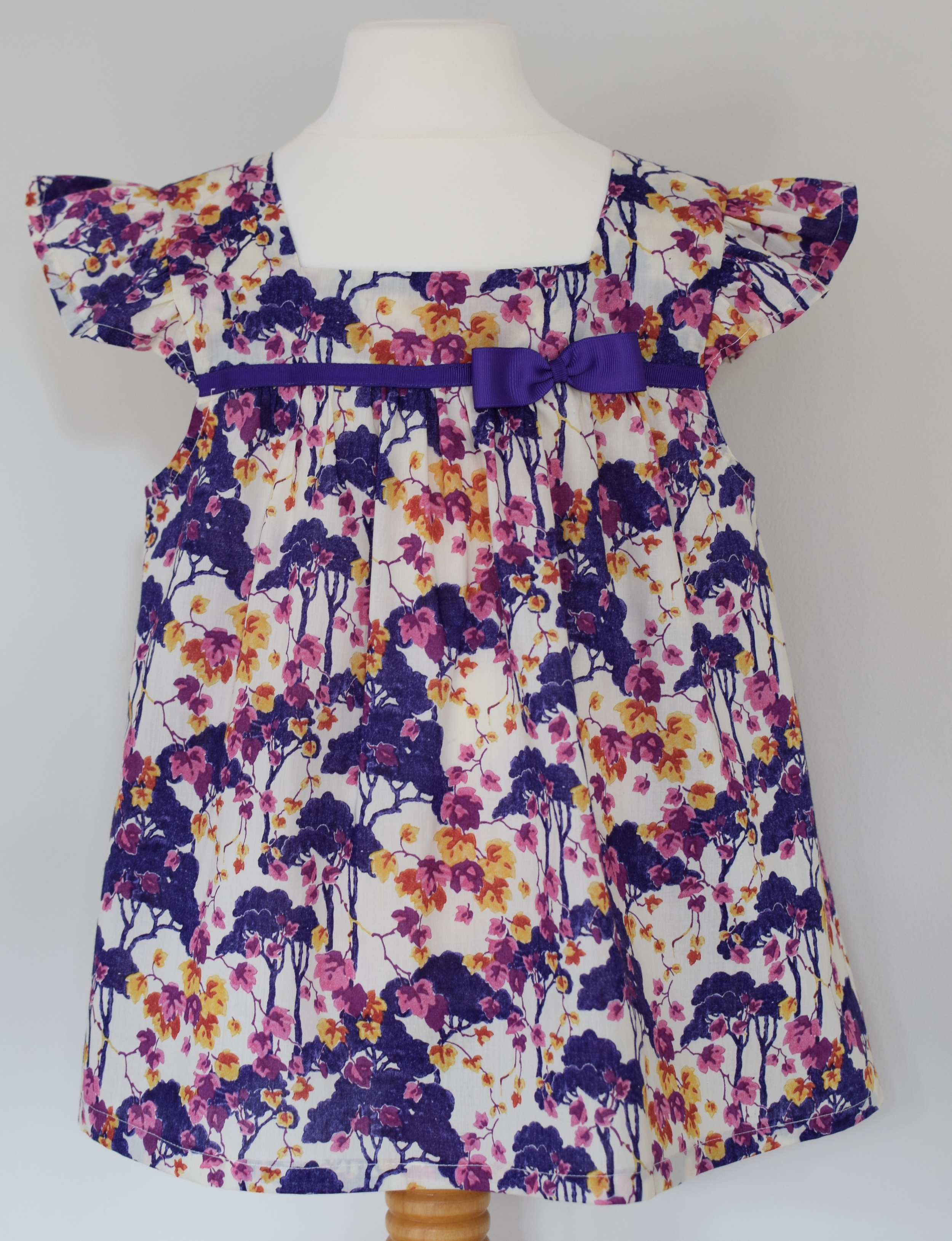 Liberty Ombrellino   Exclusive Liberty print ruffle sleeve top with square neck and a fixed purple grosgrain ribbon.  Available in size large  £35