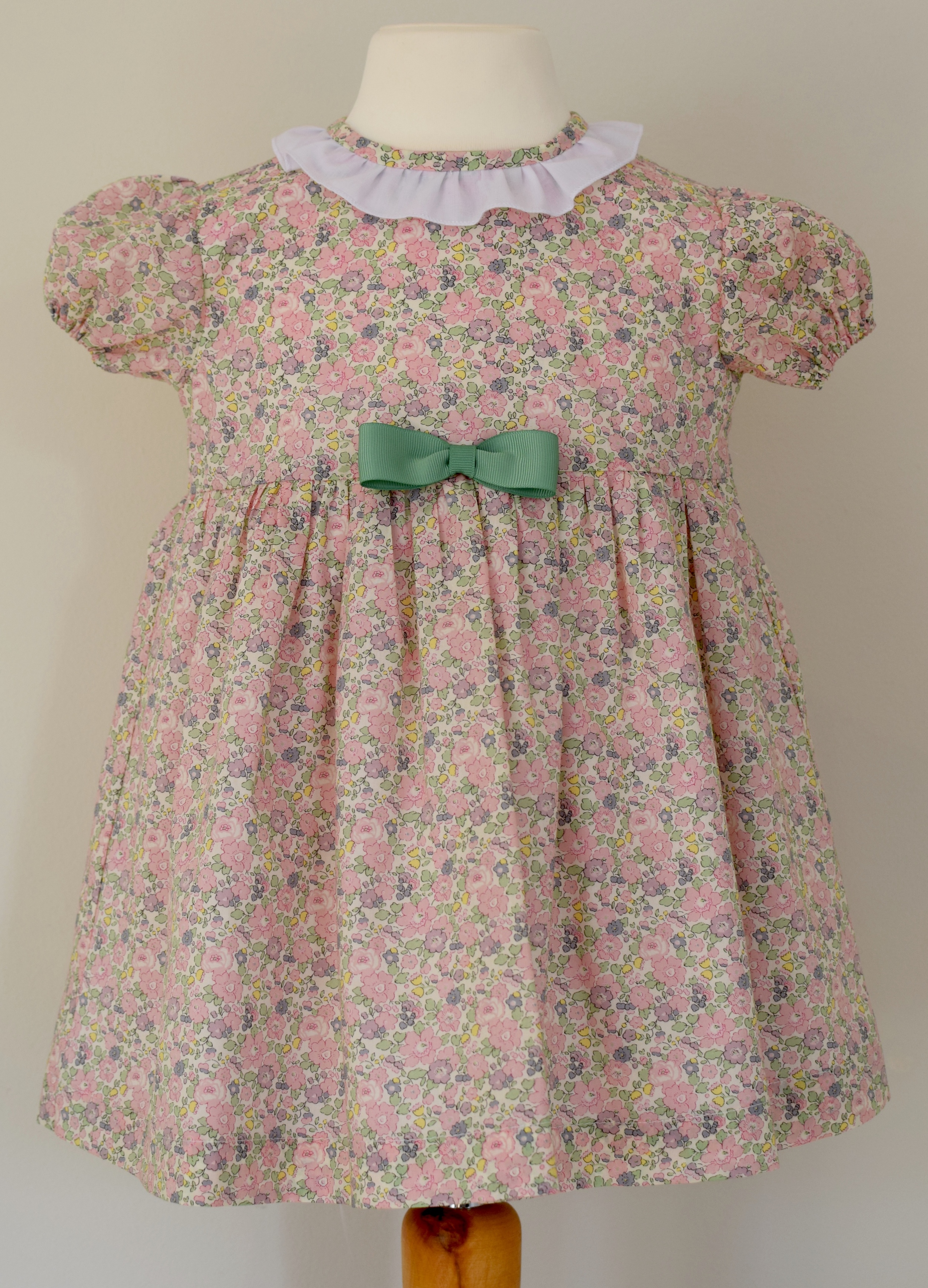 Liberty Betsy Anne pink short sleeve dress   Another gorgeous new dress for Spring Summer 16 toddlers in a dainty pale pink and green Liberty print:features include a contrasting ruffle around the neck,short sleeves and a fixed contrasting grosgrain ribbon. This dress is fully lined with a three button fastening at the back.  Available up to 3 years.  £40