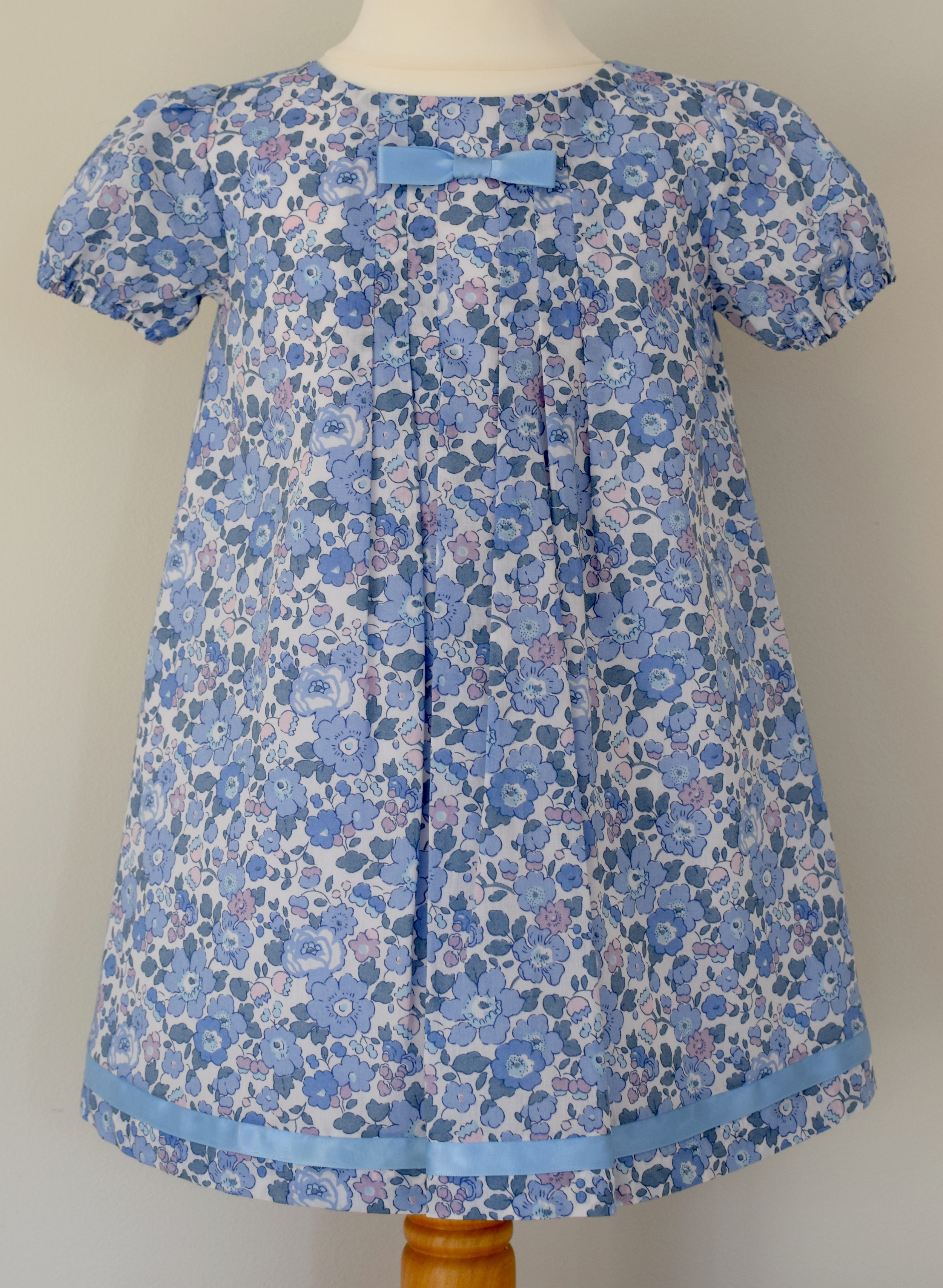 Liberty Betsy blue cap sleeve dress    Fully lined Liberty print, pleated dress with short sleeves,button fastenings at the back,fixed satin ribbon bow at front and matching satin ribbon detail at the bottom  Available up to 3 years.  £40