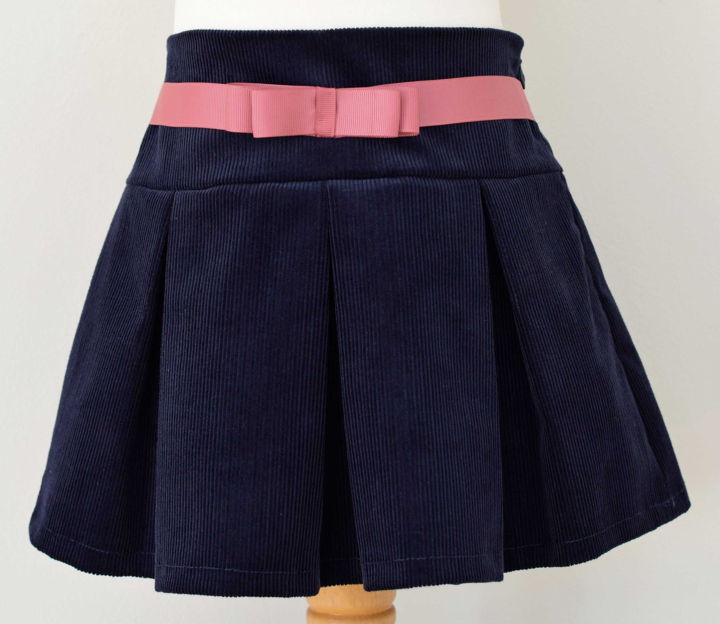 Navy corduroy skirt   Description: pretty pleats front and back, contrasting grosgrain ribbon bow, concealed zip at side, adjustable elastic waist  Sizes: available in 4y, 5y and 6y   From £32