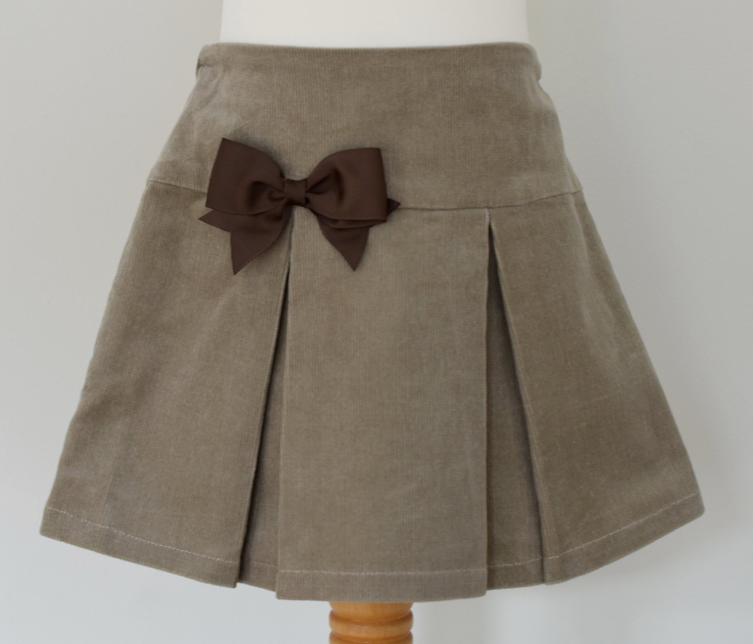 Camel corduroy skirt   Description: pretty pleats front and back, contrasting grosgrain ribbon bow, concealed zip and button at back, elastic waist  Sizes: available in 5y and 6y  £22