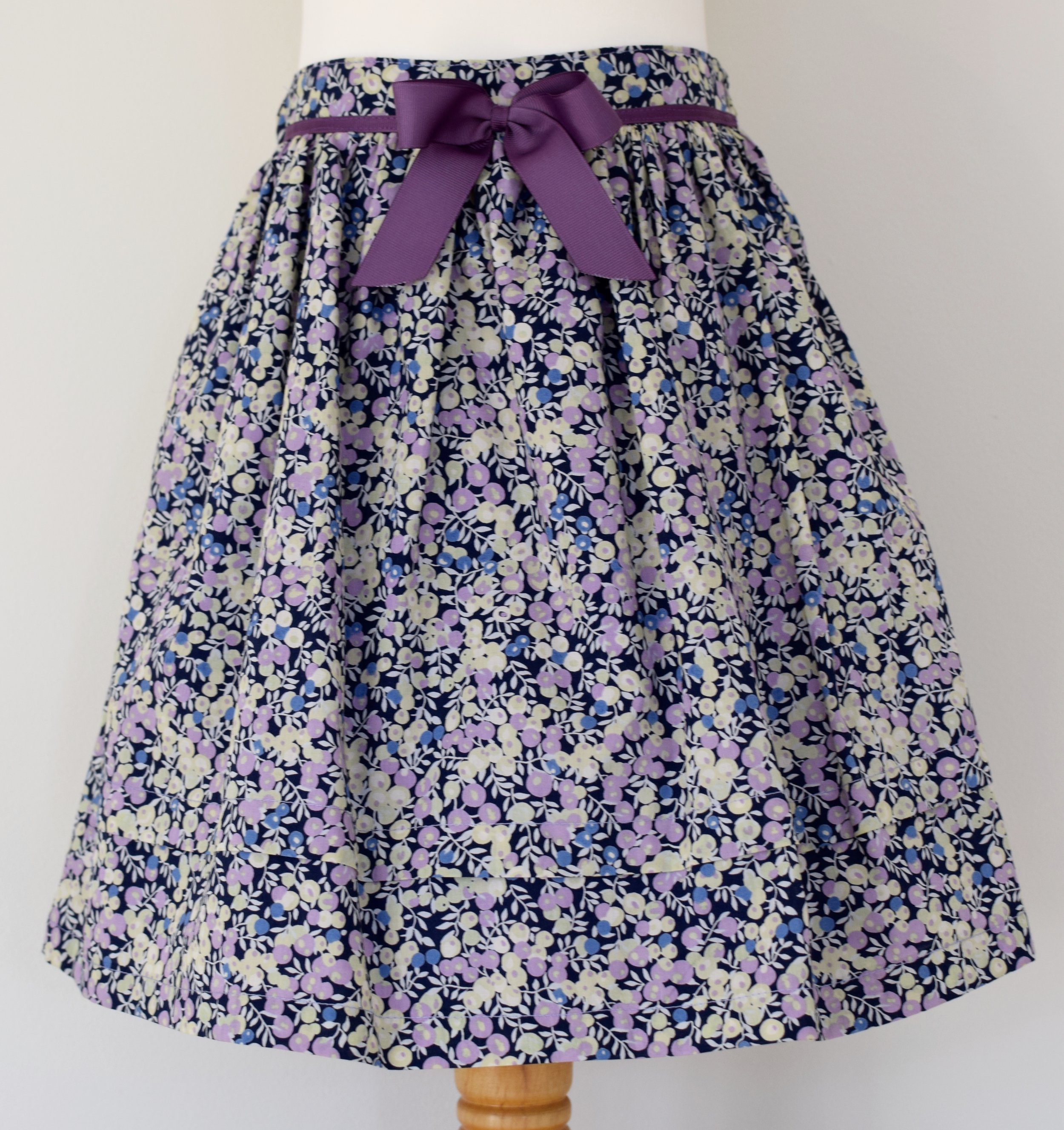Wiltshire skirt    Description: gathered skirt, contrasting purple   grosgrain ribbon bow, concealed zip at back, adjustable elastic waist   Sizes: available in 6y  £34