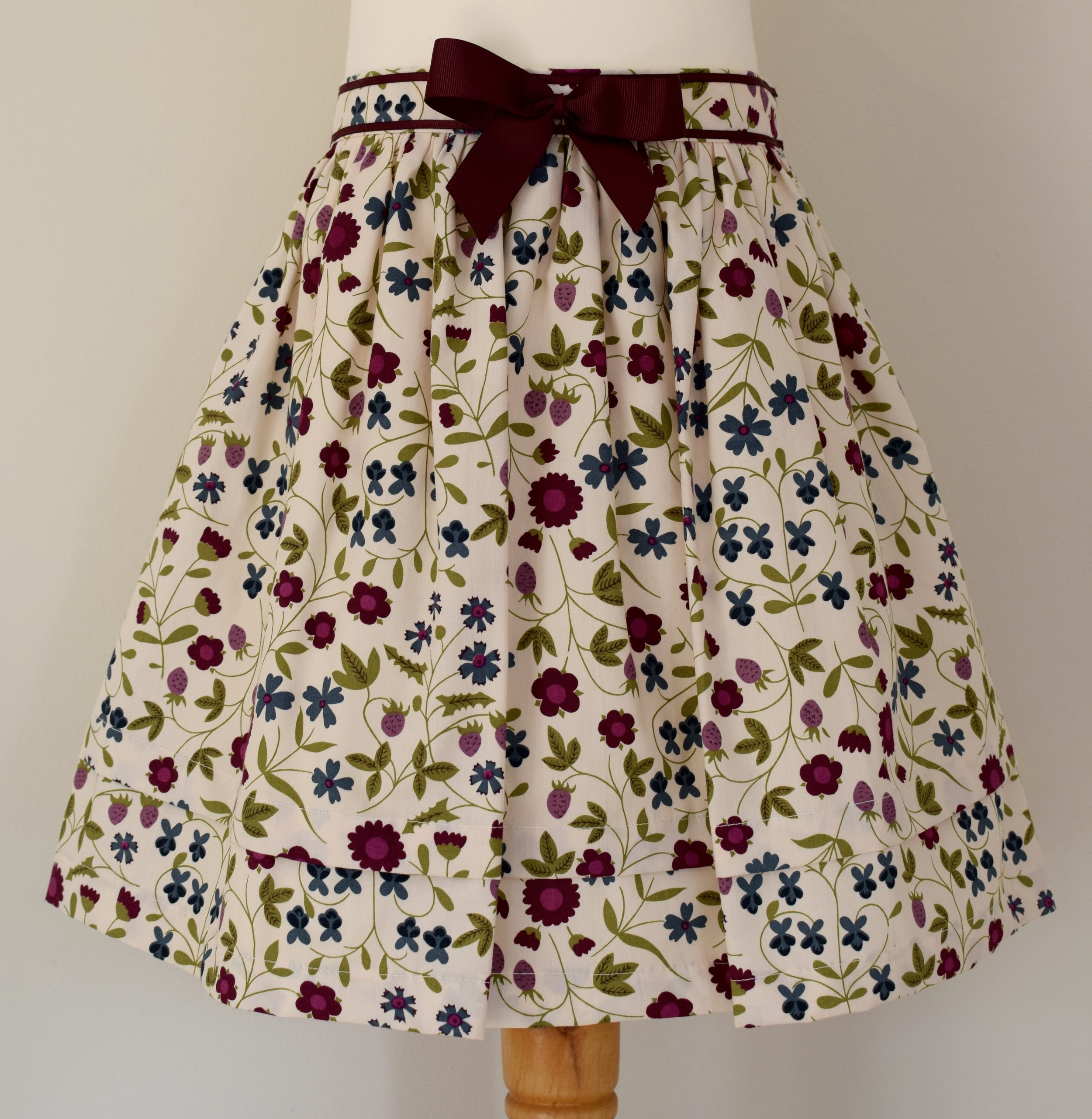 Mirabelle skirt    Description: gathered skirt, contrasting burgundy   grosgrain ribbon bow, concealed zip at back, adjustable elastic waist   Sizes: available in 6y  £34