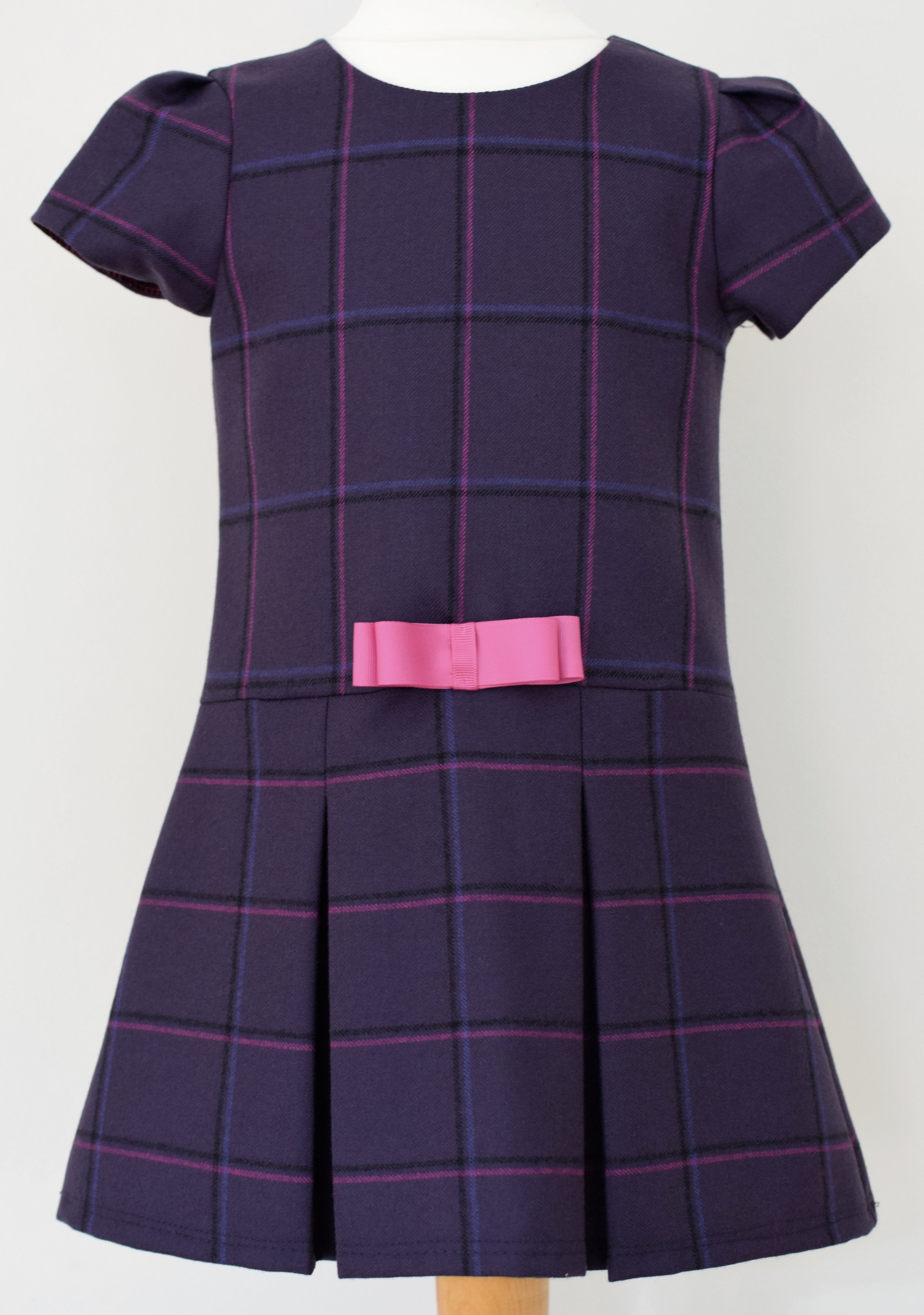 Purple check wool dress    Description: cap sleeve dress made from British designer wool with a low waist,pleated skirt, fixed grosgrain bow, concealed zip at back and fully lined.  Sizes: 3y, 4y (SOLD OUT), 5y (SOLD OUT), 6y and 7y  Price: from £38