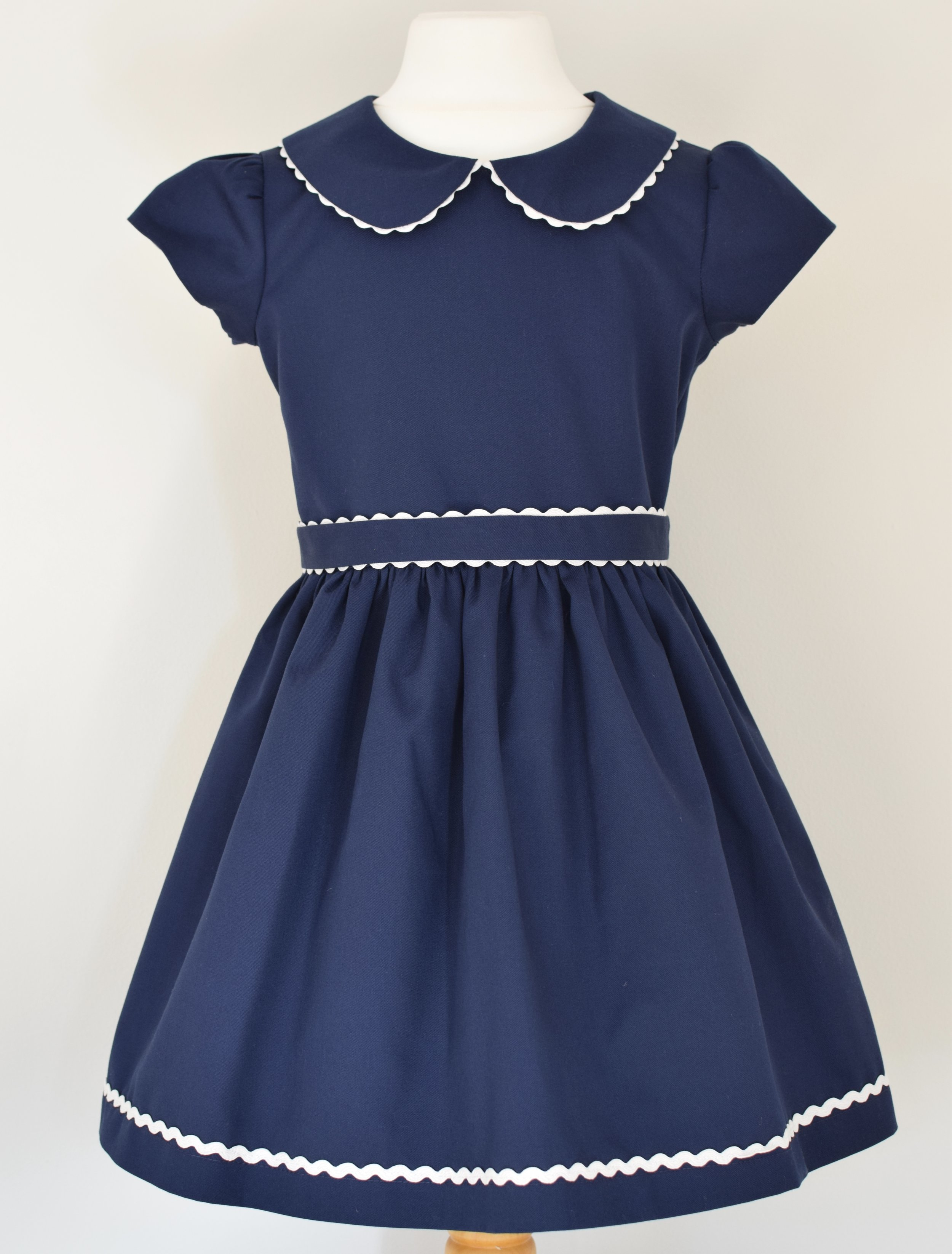 Navy twill party dress   A classic navy, cotton twill party dress with: cap sleeves,Peter Pan collar,fully lined with a concealed zip at the back and rick rack ribbon details.  Available in sizes 3y, 4y and 5y  £43