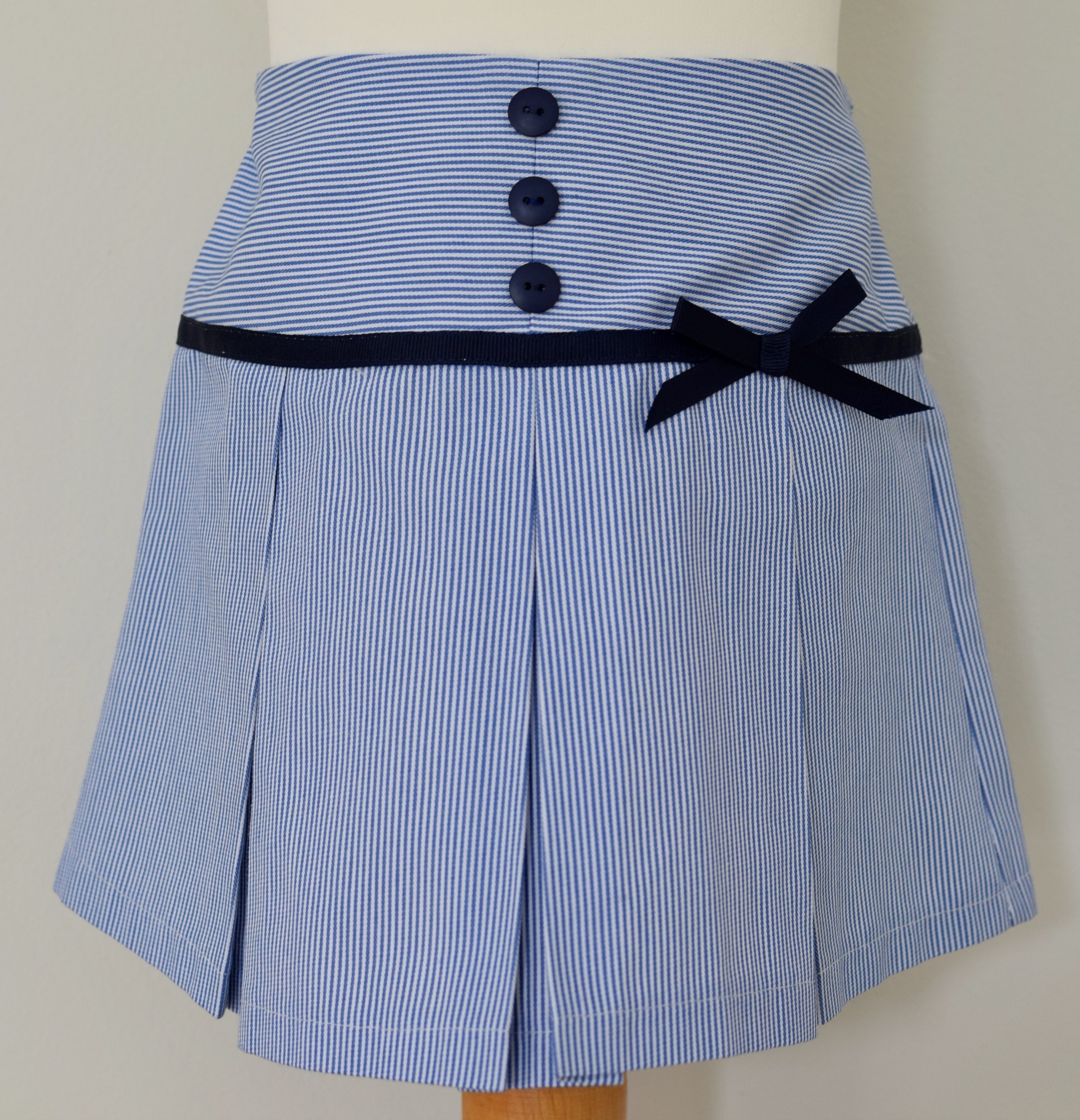 Ticking stripe pleated skirt with an elasticated and adjustable waist, fixed navy grosgrain ribbon and button detail.  £25