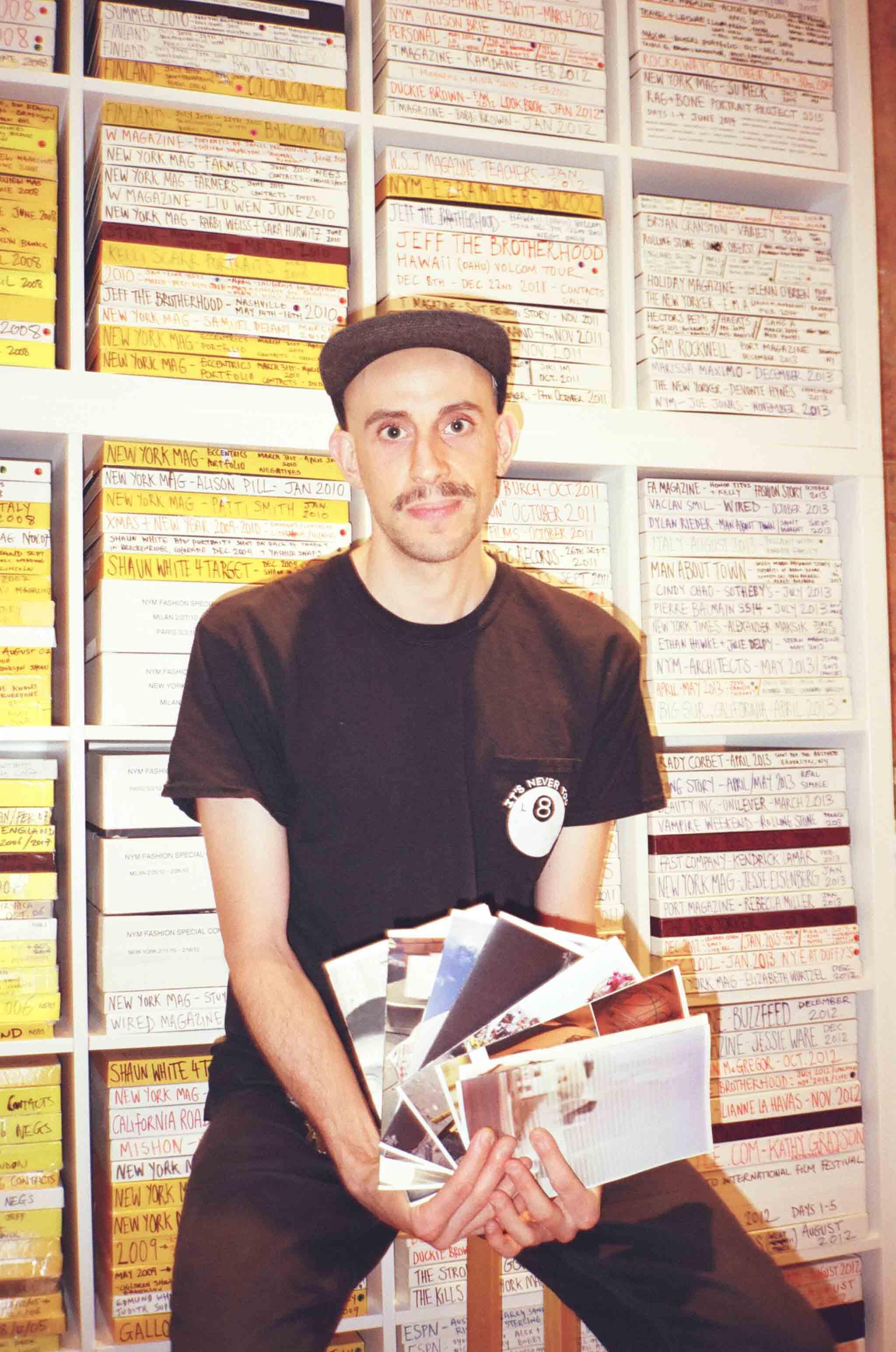 Andreas Laszlo Konrath in front of his bookcase of film negatives in his studio.