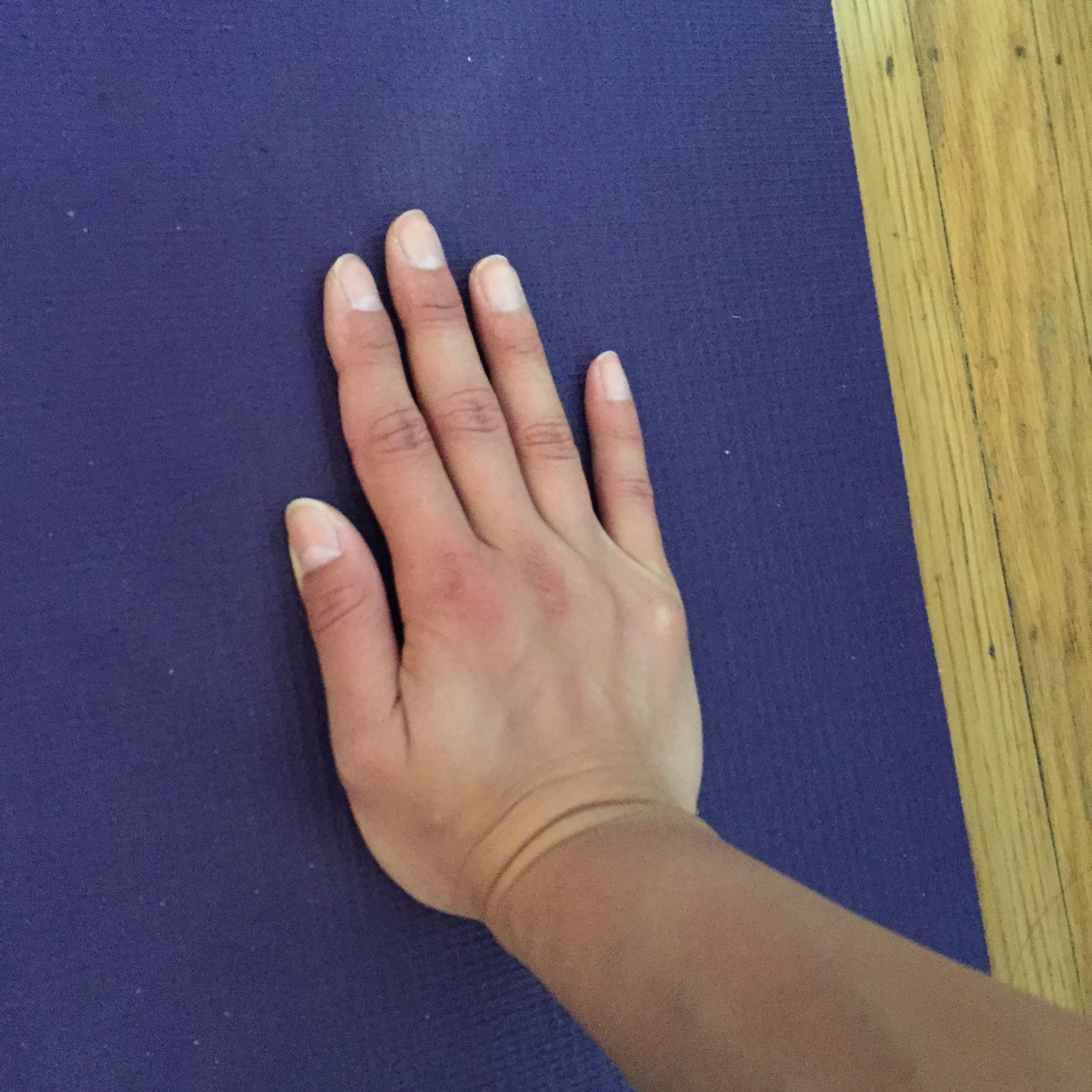 Wrong option #1: The fingers are too tightly together and not spread out to maximize the surface area of your hands grounding into the mat.