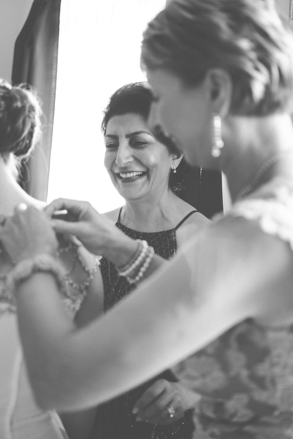 bride and mother in law putting on dress