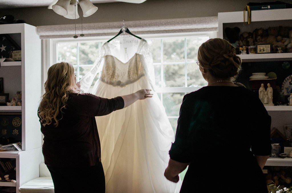 bride looking at wedding dress getting ready photo