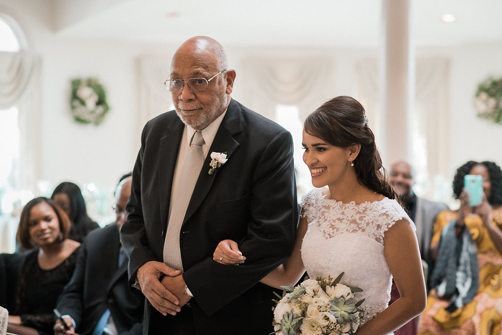bride and father of groom walking down aisle photo