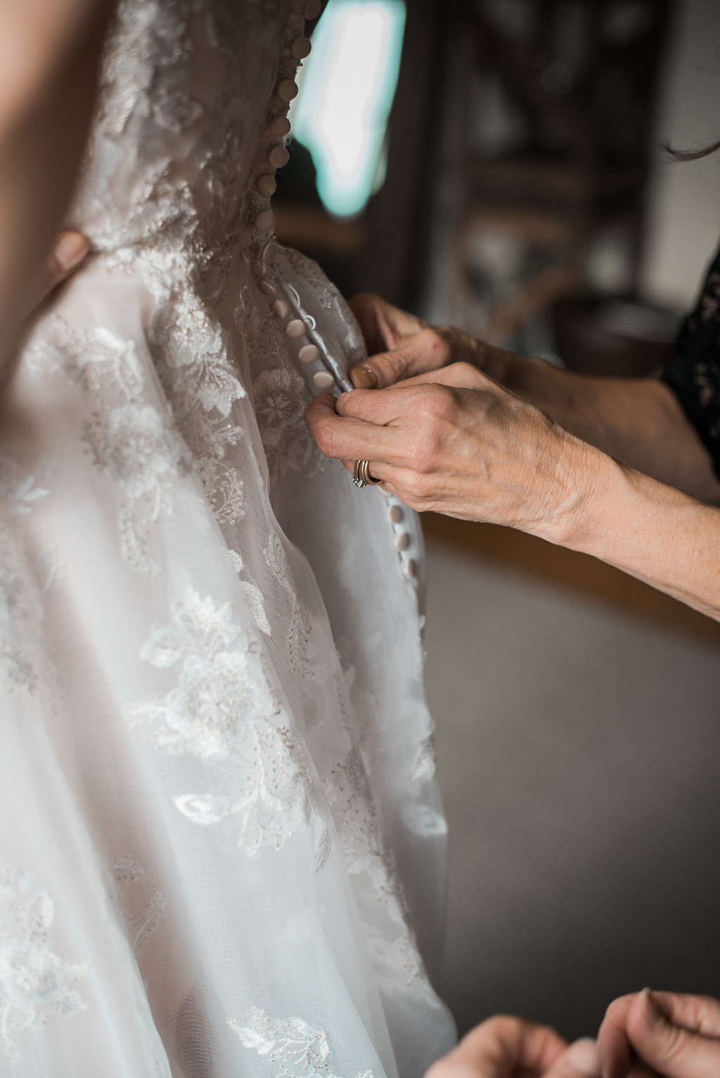 mother zippering daughters wedding dress at stone tower winery photo
