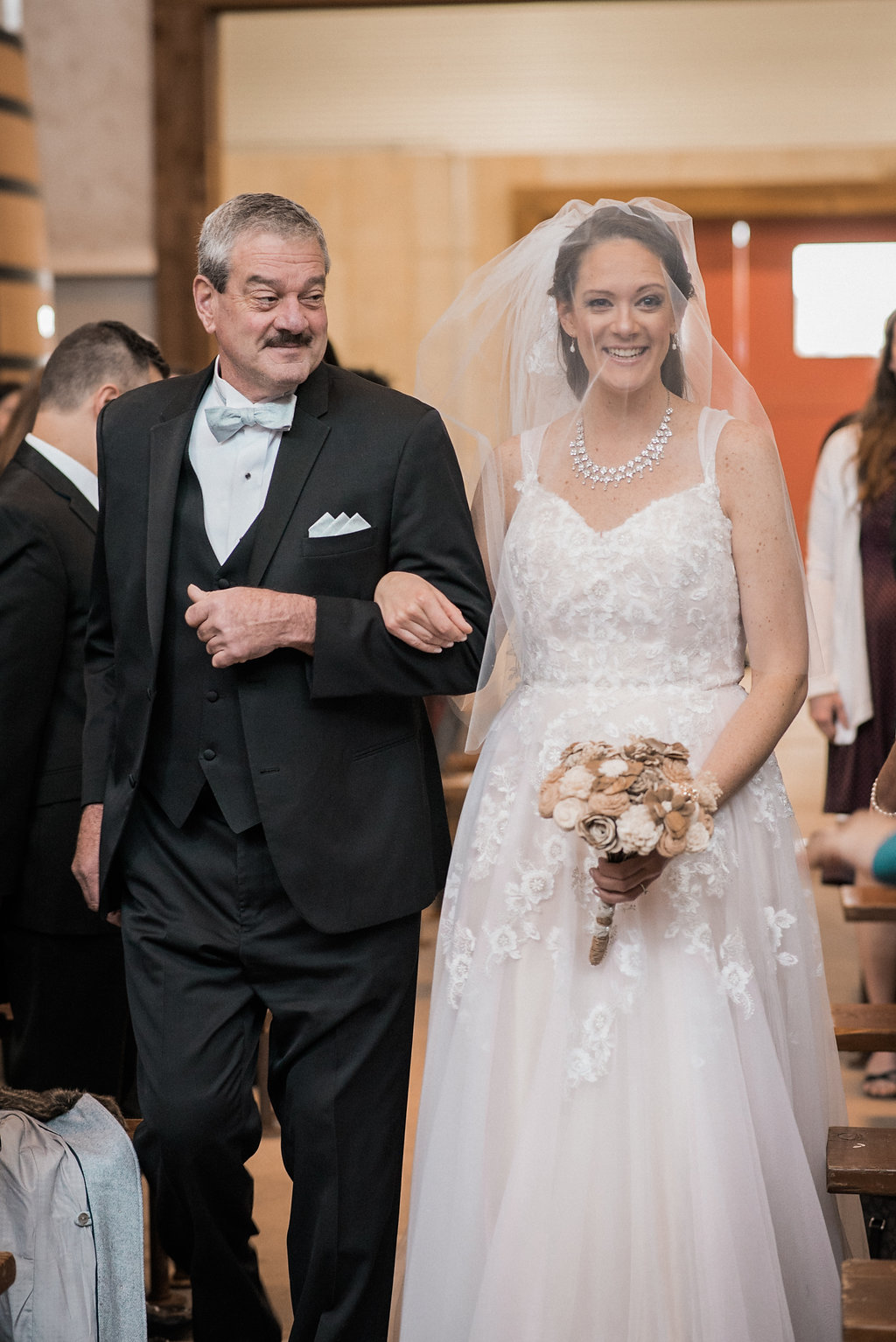 father and bride walking down stone tower tank room aisle photo