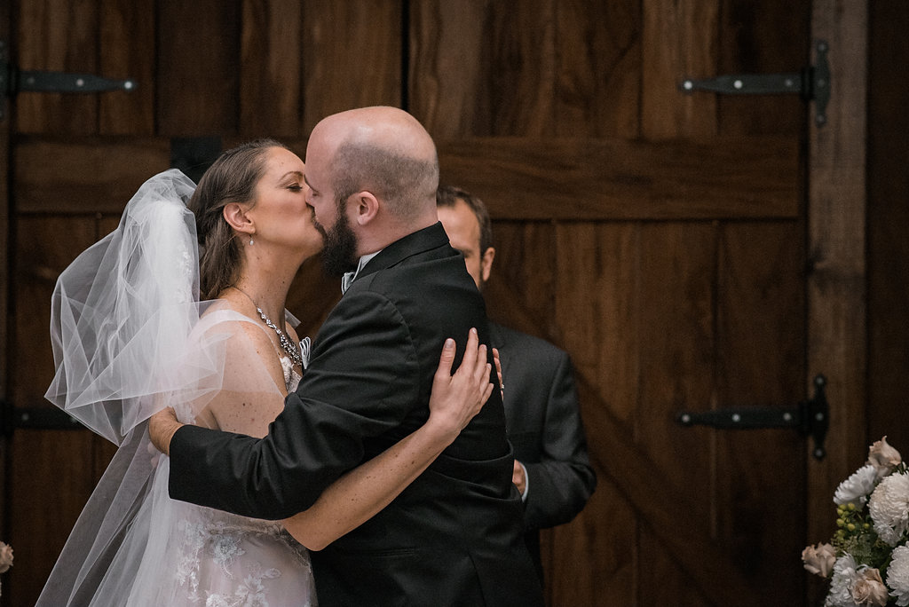 bride and groom first kiss at stone tower winery wedding photo