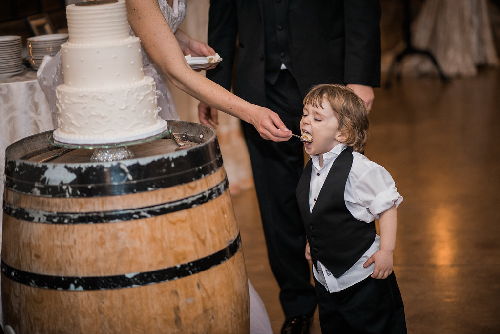bride feeding ring bearer cake at stone tower winery photo
