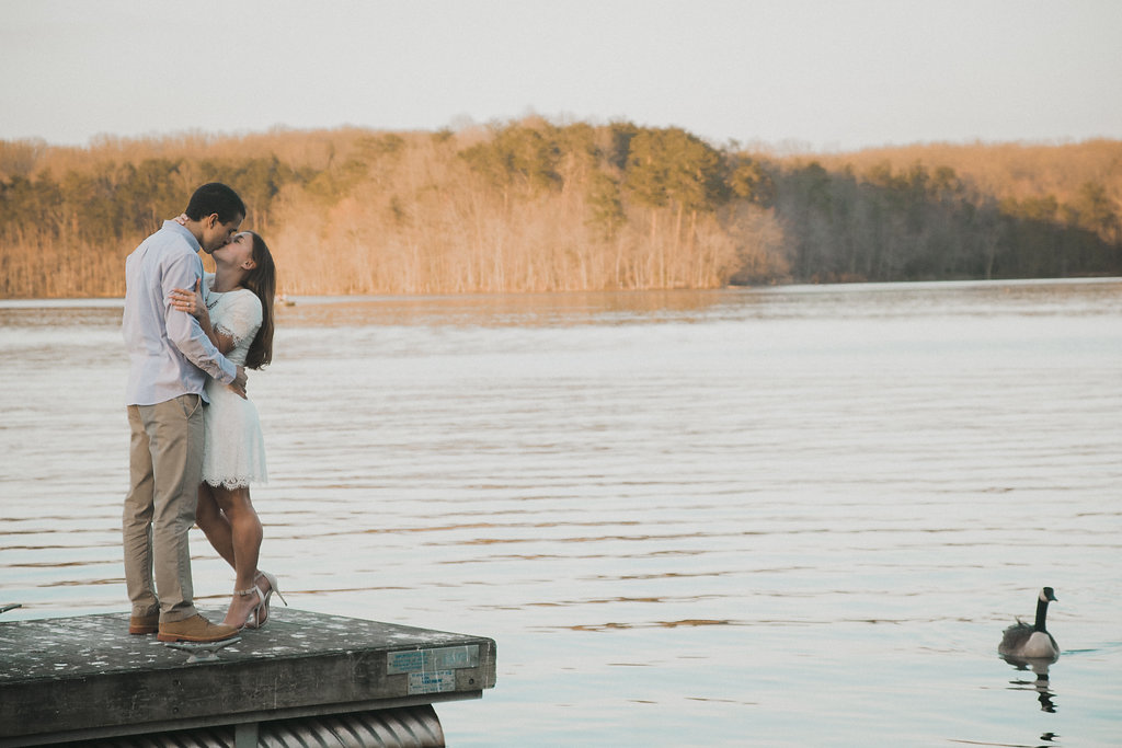 Couple kissing on dock with goose