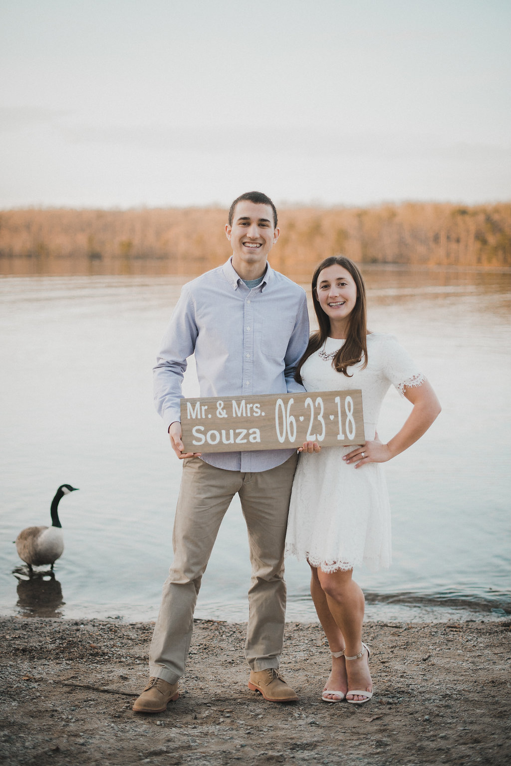 Couple with sign in front of lake