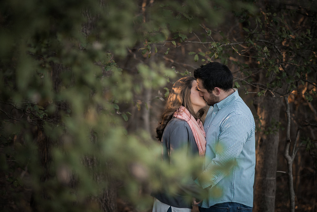 Couple kissing behind trees photo