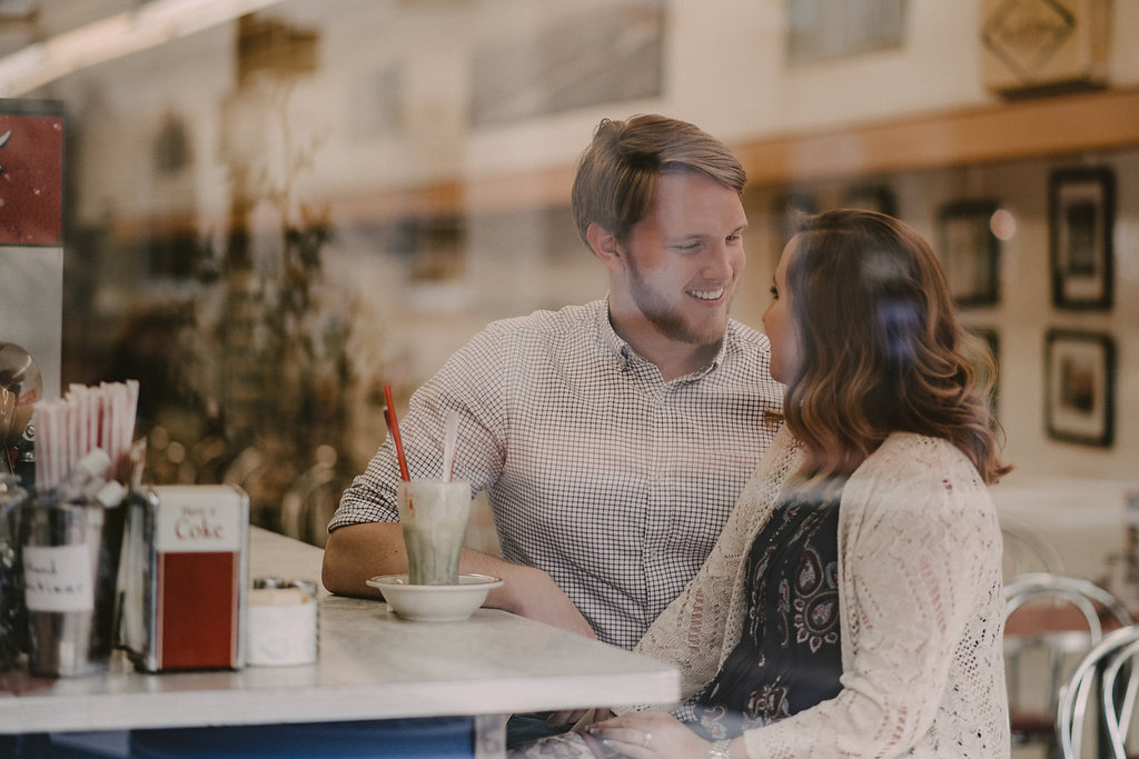Couple in ice cream parlor seen through window