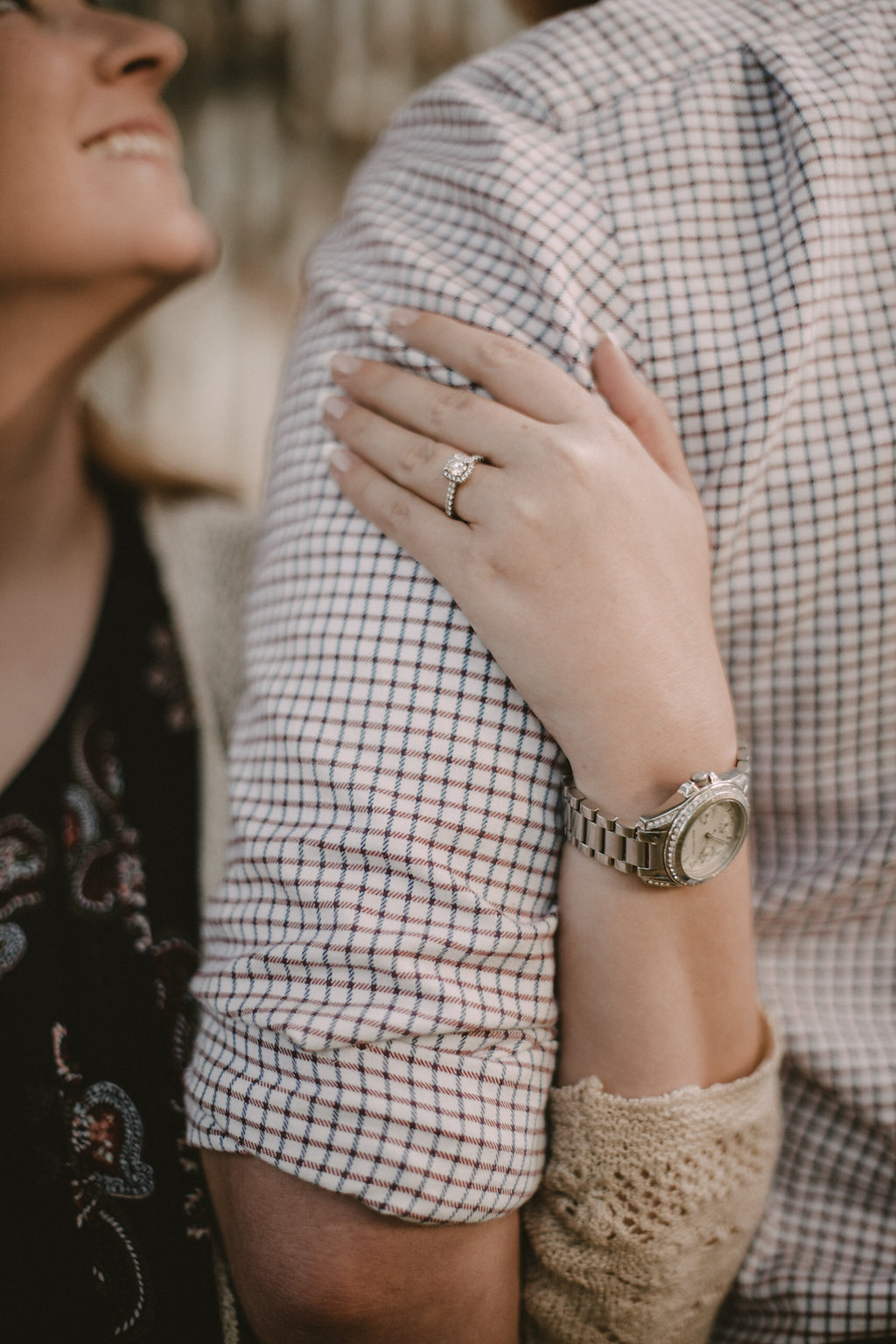 Woman's hand on arm with engagement ring