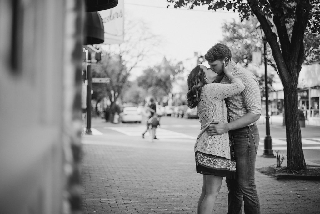 Couple kissing on sidewalk in black and white