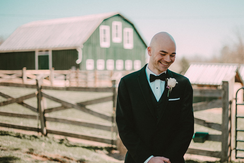 Groom smiling in front of barn