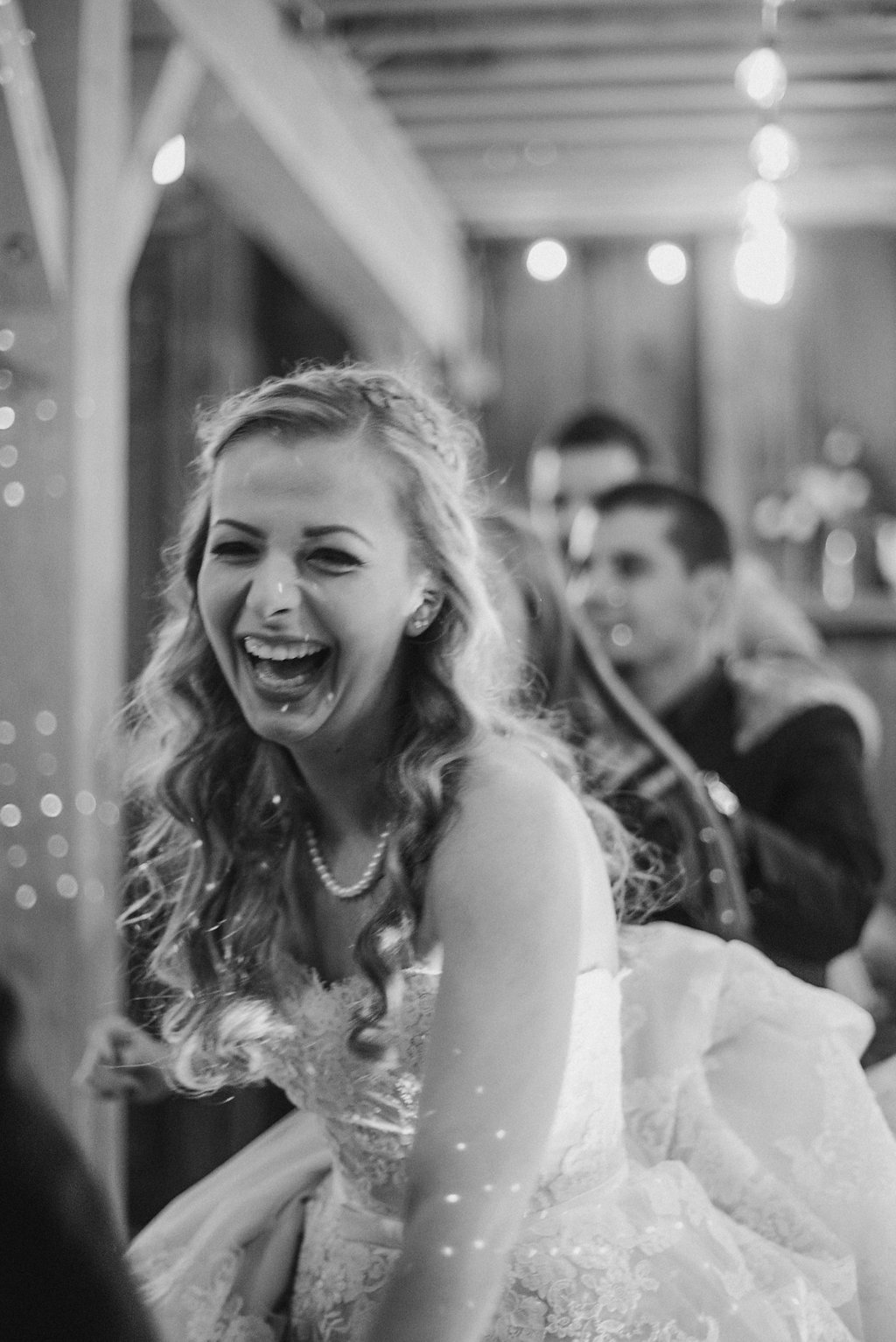 Bride laughing at wedding in black and white