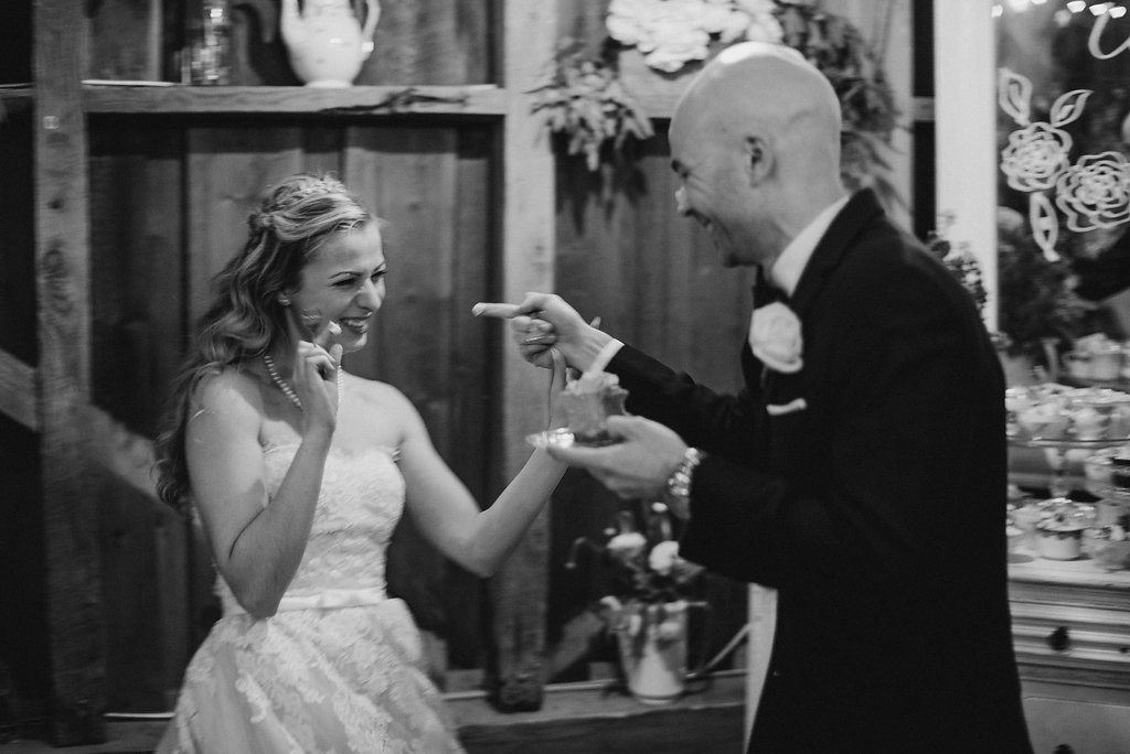 Bride and groom sharing cake in black and white