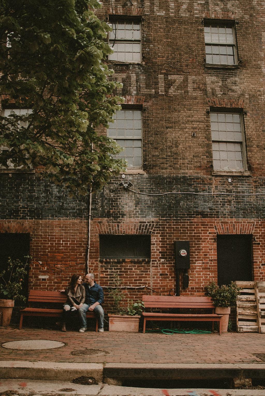 Couple sitting on bench far away