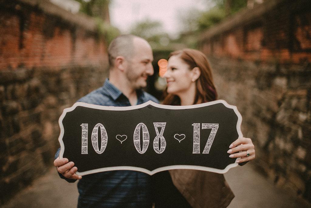 Couple holding wedding sign