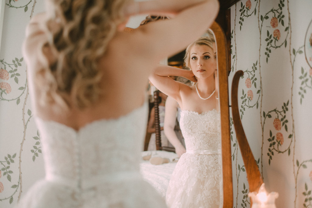 bride putting on jewelry photo