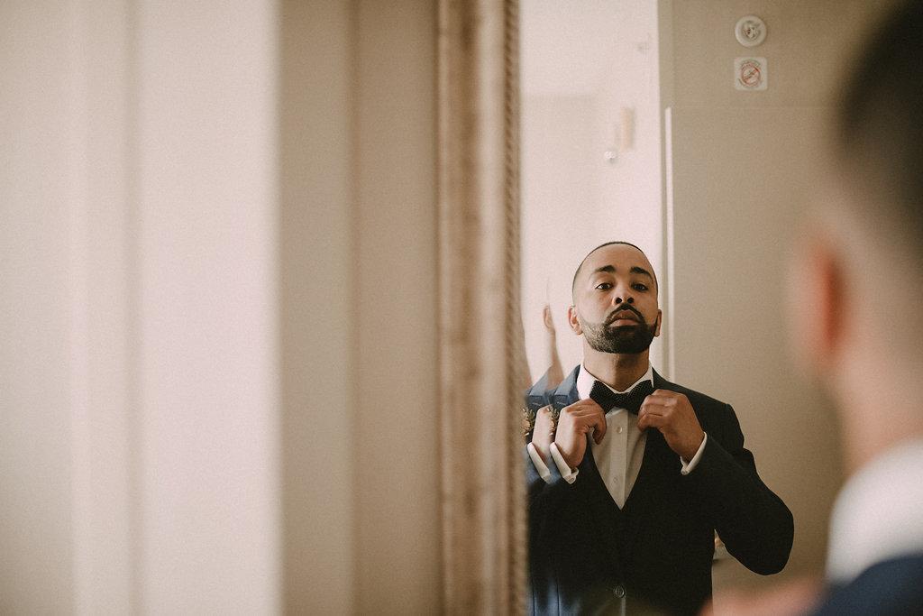 Groom tying bow tie in mirror