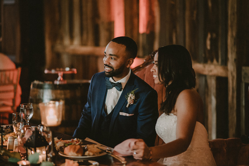 Groom and bride sitting at table at reception