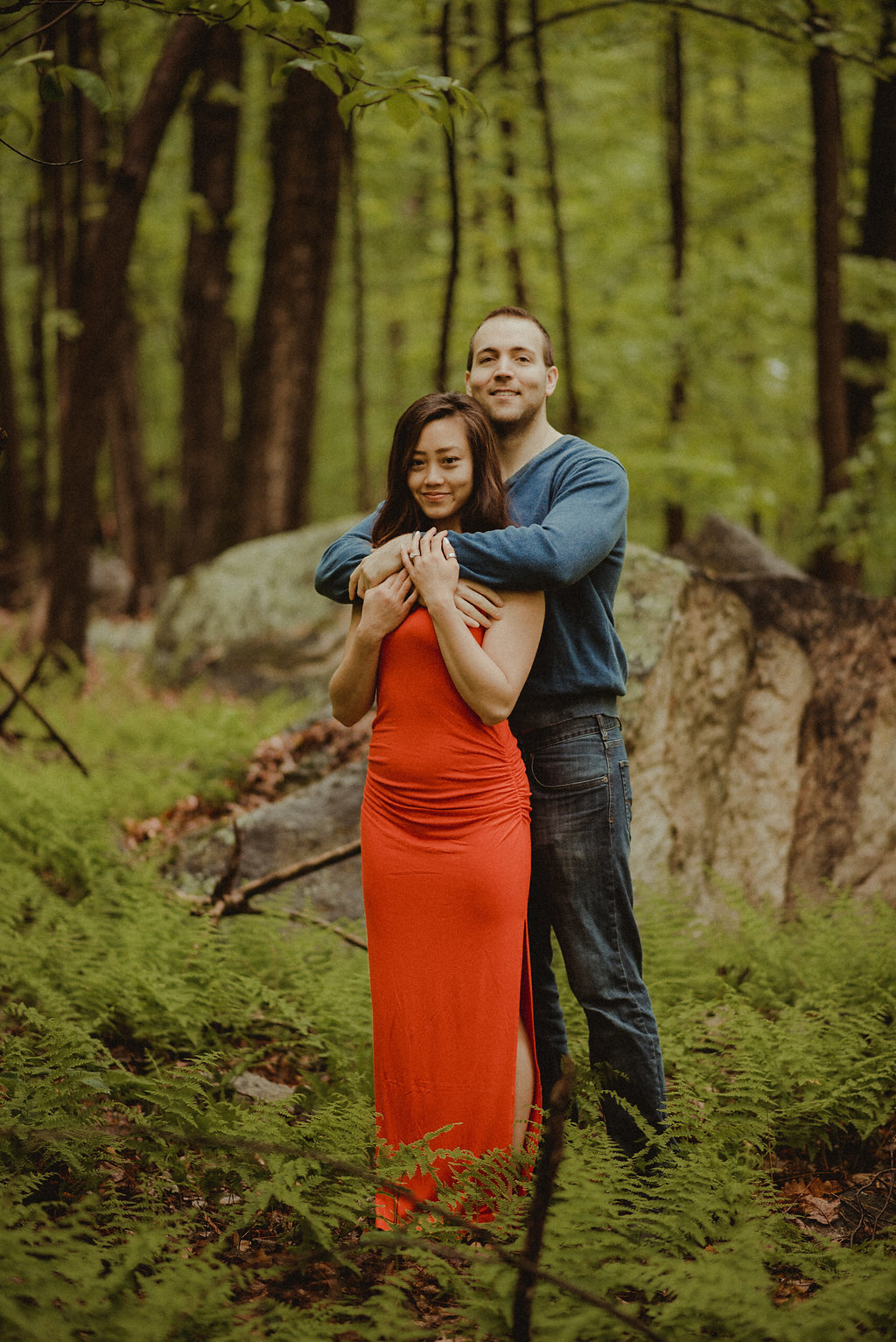 Man hugging woman in red dress.