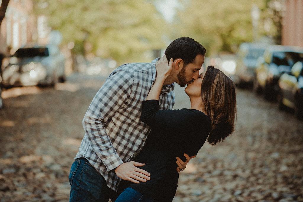 Couple kissing on cobblestone street