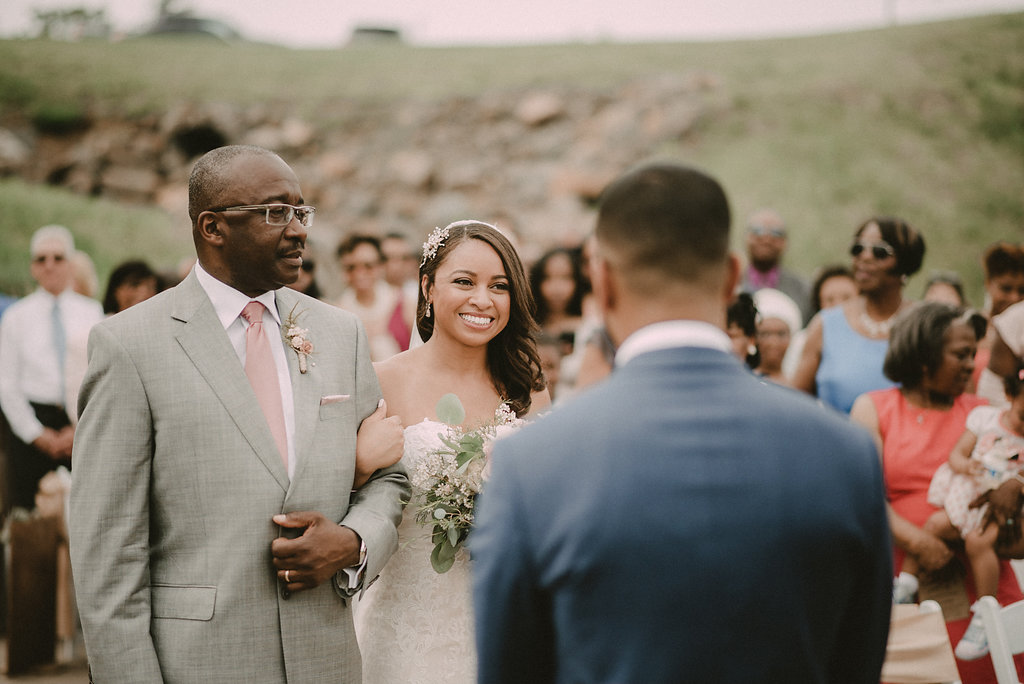 bride walking down wedding aisle with father photo