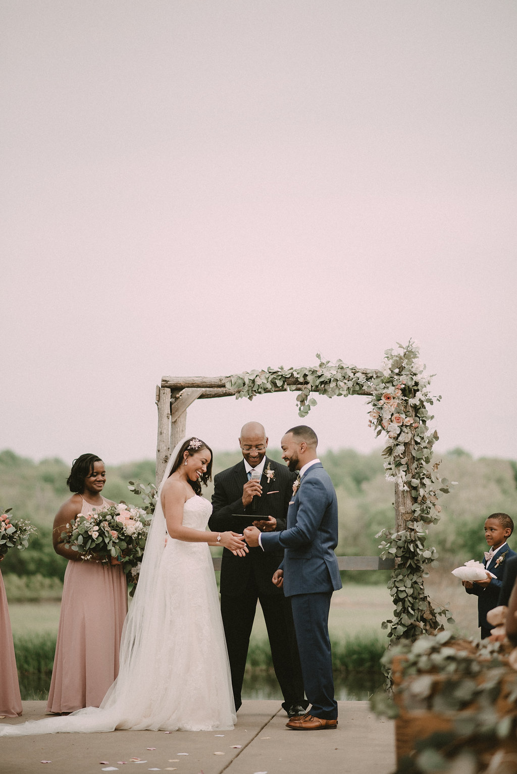 bride and groom at rustic wooden arbor photo