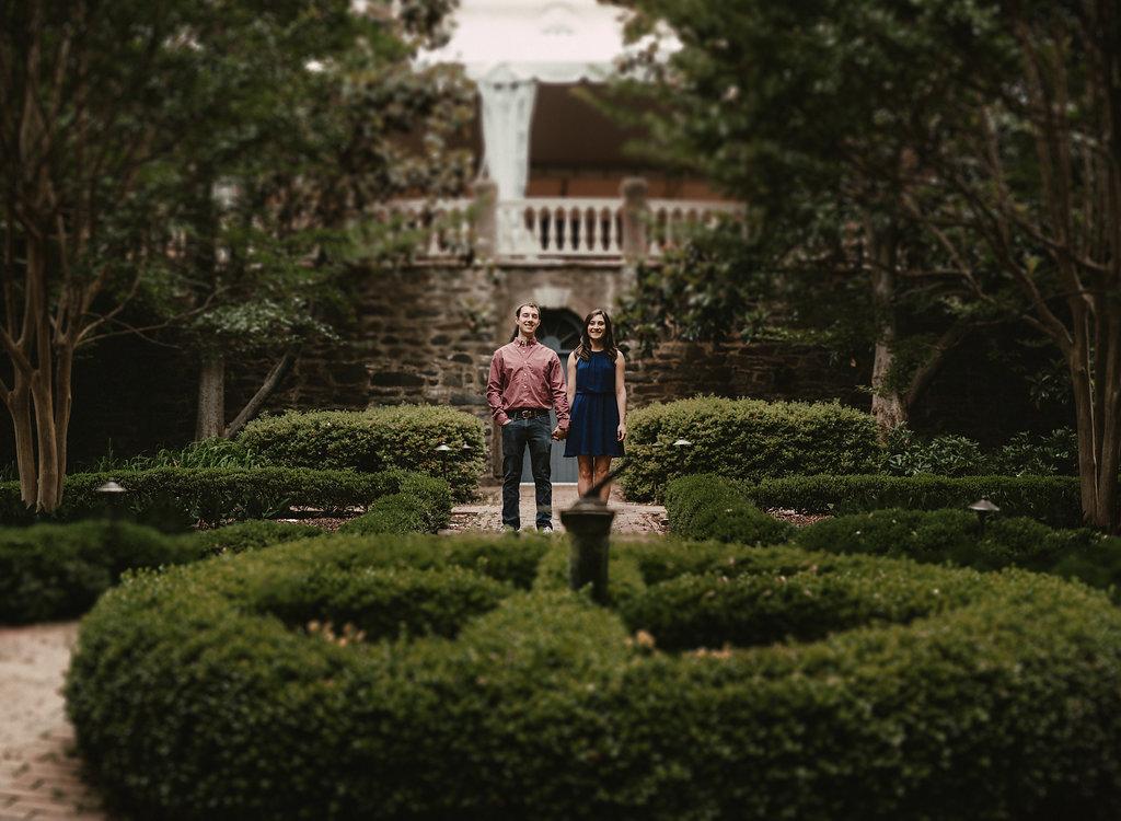 Couple standing in garden holding hands